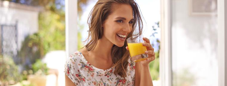 une femme boit un verre de jus d'orange riche en vitamine C